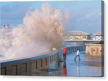 People Dodging Storm Waves Canvas Print by Ashley Cooper