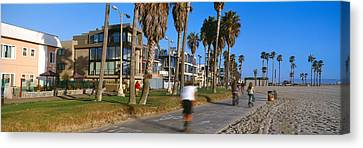 People Riding Bicycles Near A Beach Canvas Print by Panoramic Images