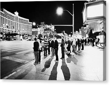 Crosswalk Canvas Print - People Waiting To Cross Las Vegas Boulevard Outside The Bellagio And Paris At Night Nevada Usa by Joe Fox