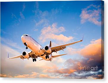 Plane Flying In Sunset Sky Canvas Print by Colin and Linda McKie