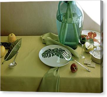Plates, Apples And A Vase On A Green Tablecloth Canvas Print by Horst P. Horst