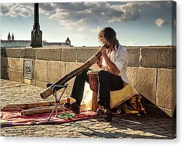 Playing Didgeridoo On The Charles Bridge. Prague Canvas Print by Jenny Rainbow
