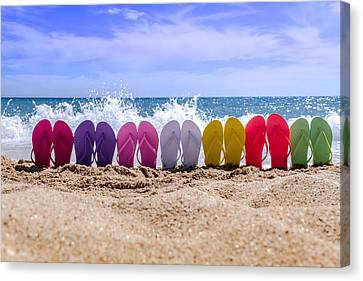 Rainbow Of Flip Flops On The Beach Canvas Print by Teri Virbickis