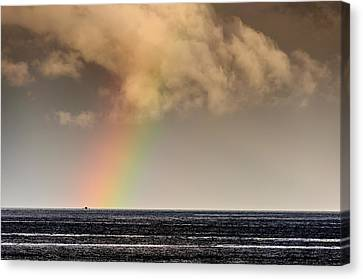 Rainbow Over A Black Ocean Canvas Print by Colin Utz