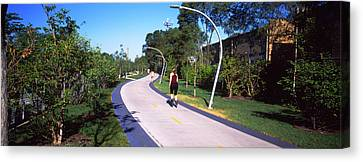 Rear View Of Woman Jogging In A Park Canvas Print