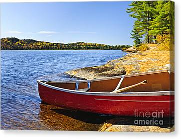 Red Canoe On Shore Canvas Print