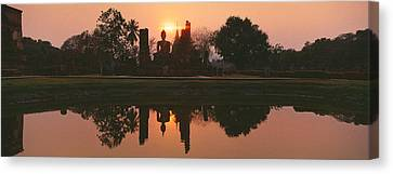Reflection Of Buddha Statue On Water Canvas Print by Panoramic Images