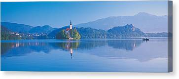 Reflection Of Mountains And Buildings Canvas Print by Panoramic Images