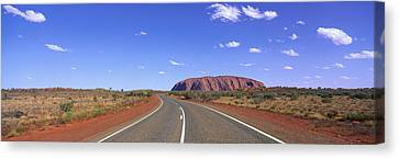 Road And Ayers Rock Australia Canvas Print by Panoramic Images