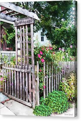 Roses On A Weathered Picket Fence Canvas Print by Susan Savad