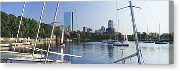 Sailboats In A River With City Canvas Print by Panoramic Images