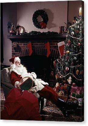 Christmas Eve Canvas Print - Santa Claus Asleep In Chair In Front by Vintage Images