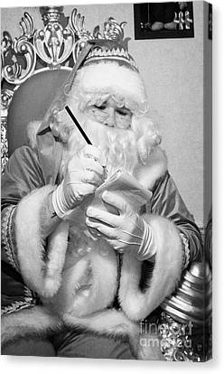 Santa Sitting On His Throne Writing A List Using Pencil And Notepad In Grotto Set Up Canvas Print