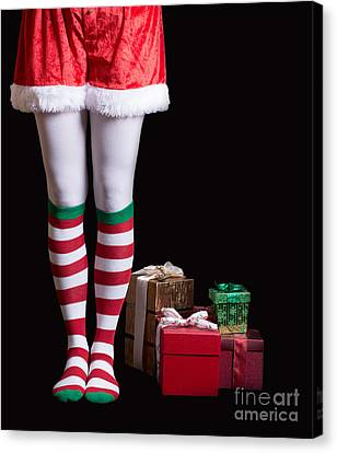 Santas Elf Legs Next To A Pile Of Christmas Gifts Over Black Canvas Print by Edward Fielding
