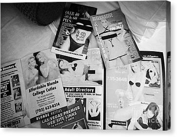 selection of leaflets advertising girls laid out on a hotel bed in Las Vegas Nevada USA Canvas Print by Joe Fox