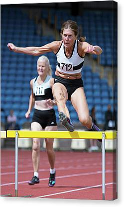 Senior Female Athlete Clears Hurdle Canvas Print by Alex Rotas