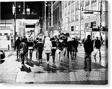 shoppers crossing corner of granville and west georgia streets at night Vancouver BC Canada Canvas Print by Joe Fox