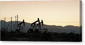 Silhouette Of Oil Rigs At Sunset Canvas Print by Panoramic Images