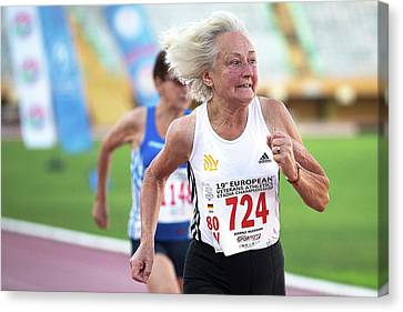 Silver-haired Female Athlete Running Canvas Print by Alex Rotas