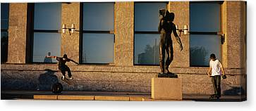 Skateboarders In Front Of A Building Canvas Print by Panoramic Images