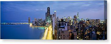 Skyscrapers Lit Up At The Waterfront Canvas Print by Panoramic Images