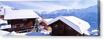 Snow Covered Chapel And Chalets Swiss Canvas Print by Panoramic Images