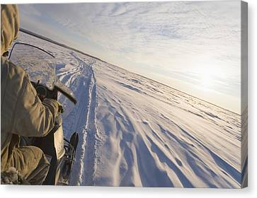 Snowmachiner Following Trail On Frozen Canvas Print by Kevin Smith