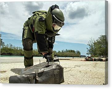 Soldier Dressed In Bomb Suit Inpecting Canvas Print by Stocktrek Images
