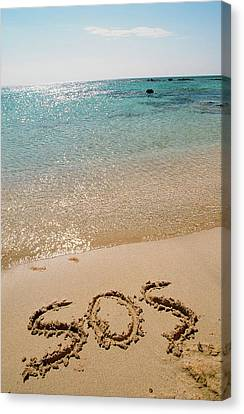 Sos Written On A Deserted Beach Canvas Print by Ashley Cooper