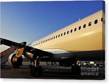 Stationary Airplane On Tarmac At Sunrise Canvas Print by Sami Sarkis