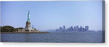 Statue Of Liberty With Manhattan Canvas Print by Panoramic Images