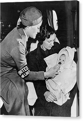 Caring Mother Canvas Print - Stewardess Feeding Baby by Underwood Archives