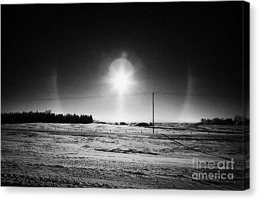 sun dog parhelion halo due to ice crystals surrounding the sun in Saskatchewan Canada Canvas Print by Joe Fox