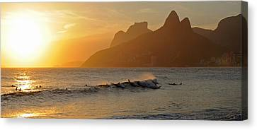 Surfers At Sunset On Ipanema Beach, Rio Canvas Print by Panoramic Images