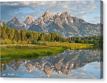 Teton Range Reflected In The Snake River Canvas Print by Jeff Goulden