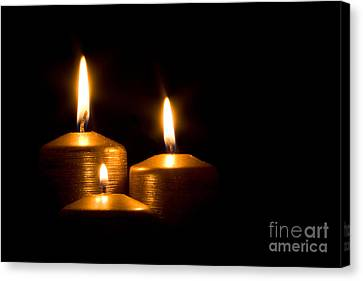 Three Golden Candles Burning In The Darkness Canvas Print by Jose Elias - Sofia Pereira