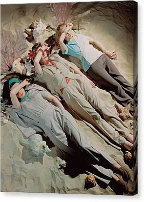Designs On Face Canvas Print - Three Models Lying Down On Sand by John Rawlings