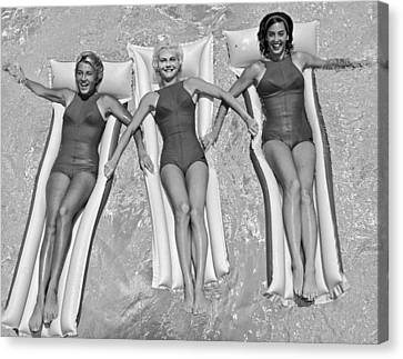 Three Women Floating In A Pool Canvas Print by Underwood Archives