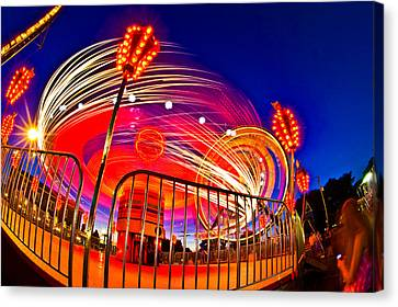 Time Exposure Of A Carnival Ride Canvas Print by Panoramic Images