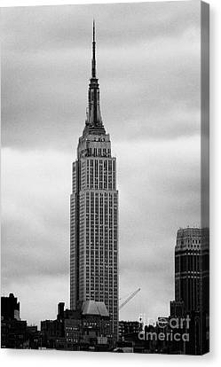 Top Of The Empire State Building Above Skyline And Grey Cloudy Sky New York City Canvas Print by Joe Fox