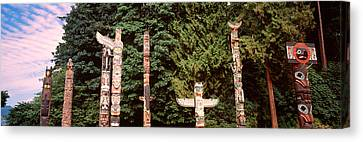 Totem Poles In A Park, Stanley Park Canvas Print by Panoramic Images