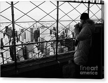 Tourist In Heavy Coat And Camera Looks At The View From Observation Deck 86th Floor Empire State  Canvas Print by Joe Fox