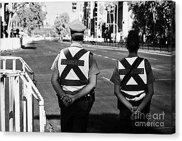 two carabineros de chile national police officers with roads closed Santiago Chile Canvas Print by Joe Fox