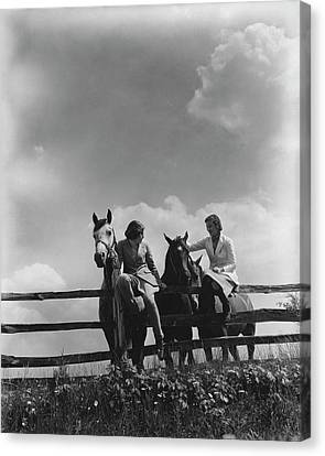 Two Women Sitting On A Fence With Horses Canvas Print