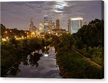 View Of Downtown Houston Skyline And Buffalo Bayou Waterway With Super Moon Rising Behind The Clouds Canvas Print by Silvio Ligutti