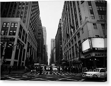 view of pedestrians crossing crosswalk on 7th Avenue and 34th Street outside macys new york city usa Canvas Print by Joe Fox