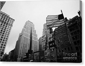 view of US flag flying on 34th street from 1 penn plaza new york city usa Canvas Print by Joe Fox