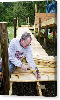 Volunteer Building A Wheelchair Ramp Canvas Print by Jim West