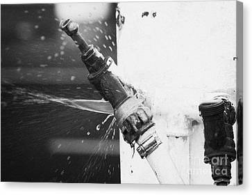 Water Escaping From A Loose Fitting Hose And Tap On Orange Post Kilkeel Harbour County Down Northern Ireland Canvas Print by Joe Fox