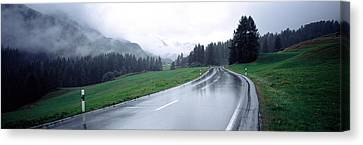 Wet Highway Passing Through A Forest Canvas Print by Panoramic Images